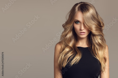Foto op Plexiglas Kapsalon Blond woman with long curly beautiful hair.