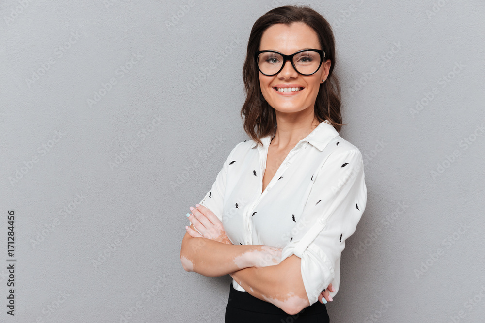 Fototapeta Smiling woman in eyeglasses and business clothes posing
