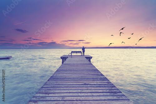 Photo sur Aluminium Caraibes Frau steht am See auf einem Steg