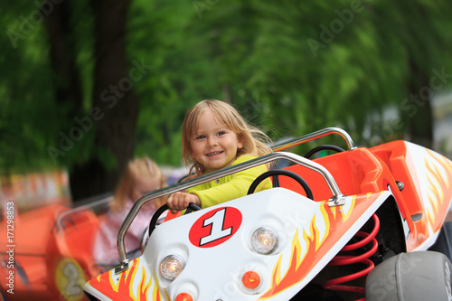 Poster Amusementspark happy little girl on roller coaster ride in amusement park
