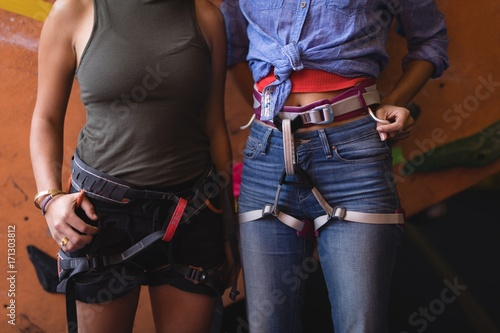Midsection of athletes wearing safety harness while standing