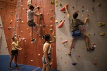 Female Athletes Standing While Male Friends Climbing Wall