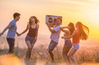 The five happy people dancing on the hill on the sunset background