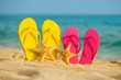Sea-stars with yellow and pink sandals stand in the sand against the background of the sea.