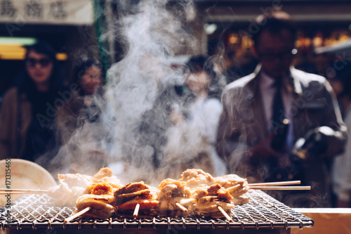 Vászonkép grilled seafood scallop and sea urchin eggs skewer with smoke, japanese street food at Tsukiji Fish Market, Japan