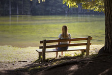 Lonely Woman Sitting On A Wood...