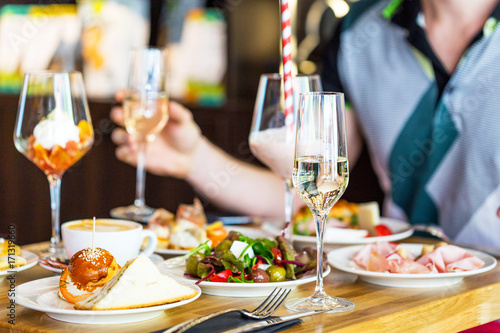 Foto auf Gartenposter Bar Table Food Lunch Bunch Variety, Mans Hand with Glass of Champagne