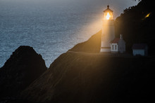 The Light Of Heceta Head Lighthouse Shines At Dusk