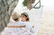 asian woman and man sitting on hammock in sweet moment on the beach