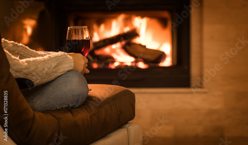 Fotografía Young woman sitting at home by the fireplace and drinking a red wine