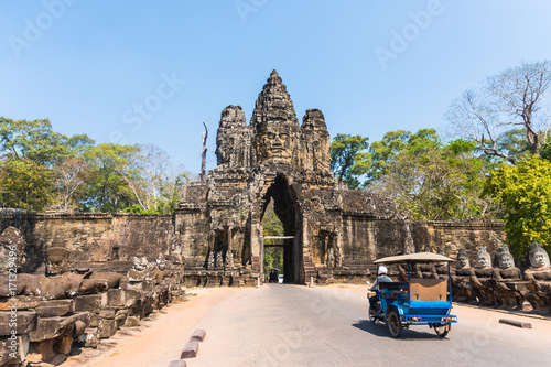 Fototapeta premium Tuk tuk i angkor thom gate w Kambodży siem reap