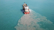 Suction Dredger Ship Working Near The Port - With Mud, Pollution, Brown Muddy Water - Aerial Tip Down Shot