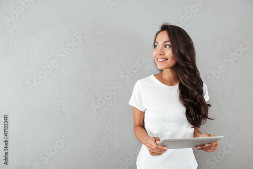Obraz Pretty smiling asian woman holding tablet computer - fototapety do salonu