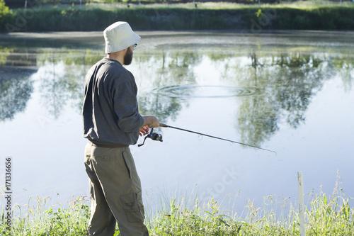 Fotobehang Vissen Wędkarz łowi ryby na spinning. Ściąga żyłkę kołowrotkiem.