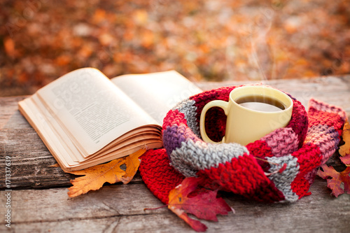 Open book and yellow tea mug with warm scarf