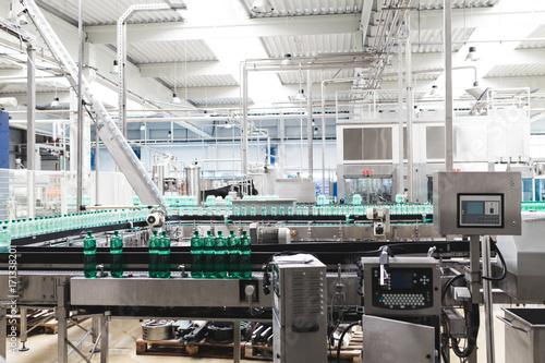 Fototapeta Bottling plant - Water bottling line for processing and bottling pure mineral carbonated water into bottles. obraz na płótnie
