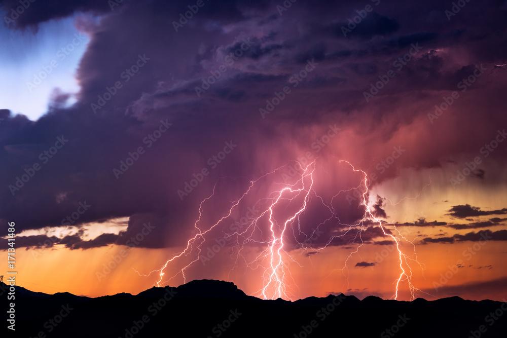 Fototapety, obrazy: Lightning bolts strike from a sunset storm