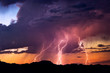 canvas print picture - Lightning bolts strike from a sunset storm
