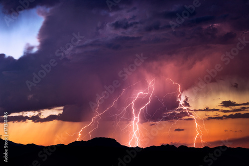 Foto op Canvas Onweer Lightning bolts strike from a sunset storm
