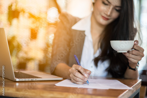 Valokuva  Young female freelancer working on marketing plan at coffee shop
