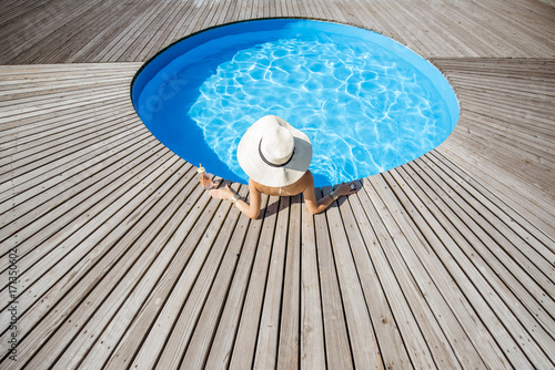Photo  Woman in big sunhat with cocktail drink relaxing at the round swimming pool with blue water outdoors