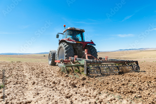Платно  agricultural tractor in the foreground with blue sky background.