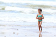 The small beautiful girl with plaits in a turquoise bathing suit on seacoast