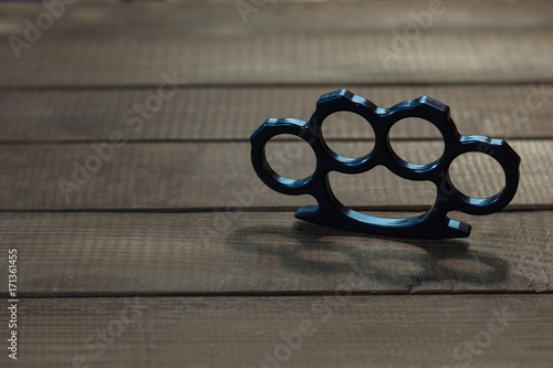 Brass Knuckles On A Beautiful Brown Wooden Background Buy This