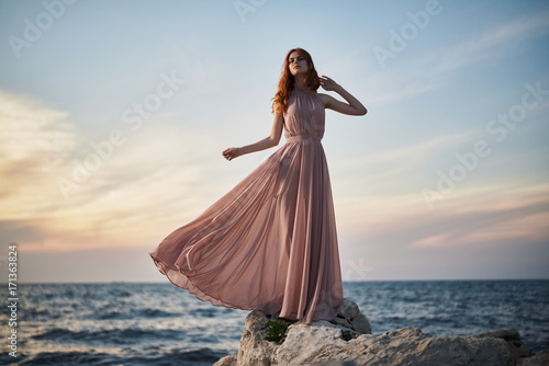 Fotografering woman in a long pink dress on the beach, sunset