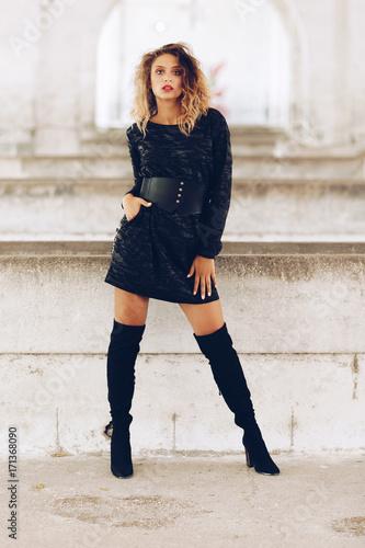 Plakat Stylowa modna dziewczyna z długimi blond włosami, stylowa czarna sukienka. Moda modna kobieta koncepcja
