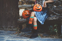 Crop Little Girl In Witch Costume Sitting On Bench