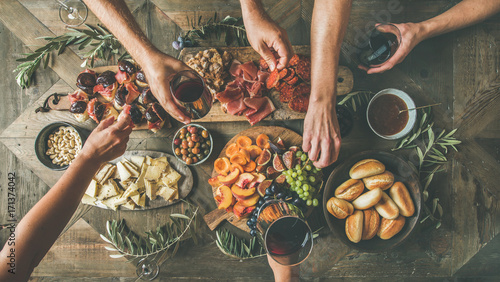 Fotografia Flat-lay of friends hands eating and drinking together