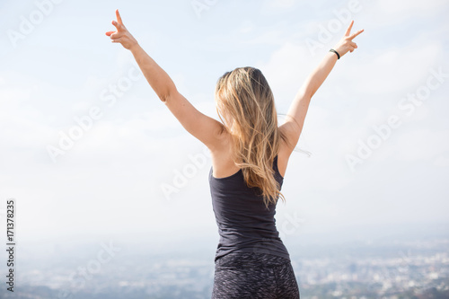 Photo  Slender girl standing on the top of the hill showing victory signs with her fing