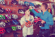 Man with teenager son buying protective helmet
