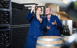 Two attentive winery workers in aging section of factory