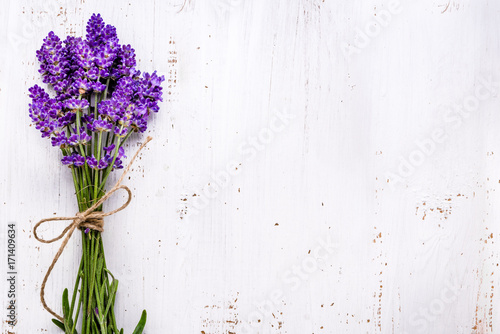 fototapeta na szkło Fresh flowers of lavender bouquet, top view on white wooden background