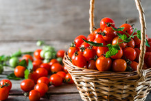 Organic Tomatoes Called Cherry Tomato In The Basket On Wooden Table, Farm Fresh Produce Freshly Harvested From Local Farmers