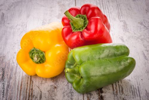 Insieme di peperone rosso, peperone giallo e peperone verde isolati su un tavolo Wallpaper Mural