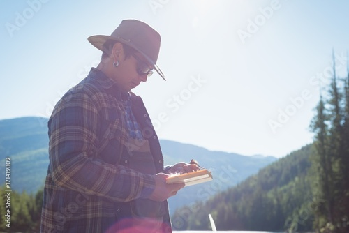 Side view of man holding box while standing against sky