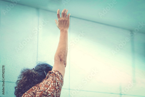 Vintage tone of old woman christian raised her hand in