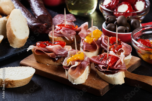 Spanish tapas with slices jamon serrano and grilled pepper. Also olives, salami, pickled onions, and peppers stuffed with cheese