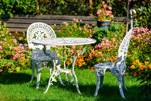 White Metal Outdoor Furniture Group In Garden. One Table And Two Chairs In Vintage Style With Autumn Flowers In Background.