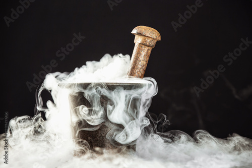 Photo  Closeup rusty vintage mortar filled with magic potion and deep smoke around at black background