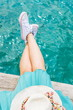 Woman legs above water on a dock