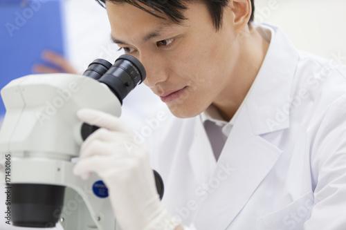 Male scientist using microscope
