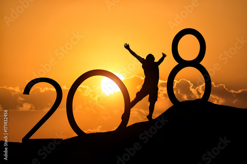 Fotografia, Obraz  Silhouette person jumping over 2018 on the hill at sunset