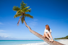 Teenage Girl Sitting On A Palm...