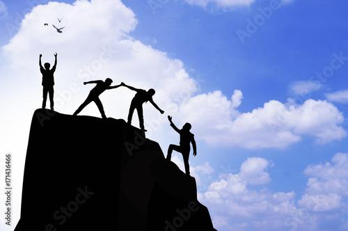 Láminas  silhouette people helping hand to climb mountain rock, concept as winner, improv