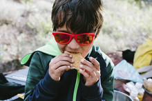 Boy In Sunglasses Eating Sandwich At Campsite