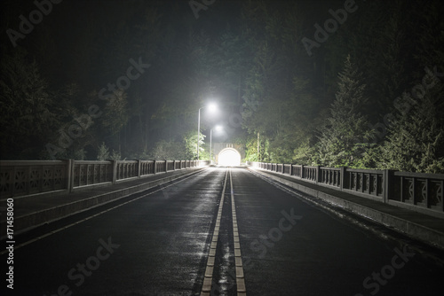 View of empty road passing through tunnel during night
